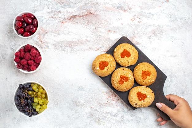 Vista dall'alto piccoli biscotti di zucchero deliziosi dolci per il tè con la frutta sulla scrivania bianca torta biscotti zucchero torta dolce