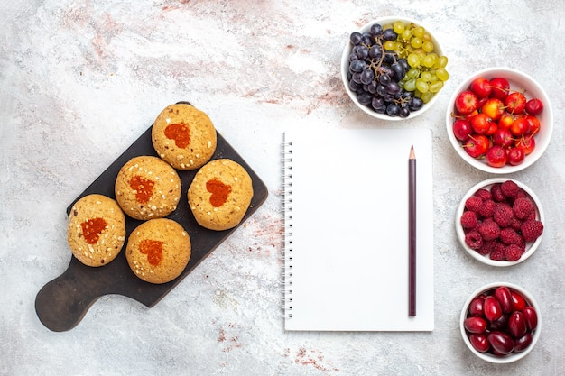 Vista dall'alto piccoli biscotti di zucchero deliziosi dolci per il tè con la frutta sulla superficie bianca torta biscotto zucchero biscotto torta dolce