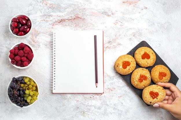 Vista dall'alto piccoli biscotti di zucchero deliziosi dolci per il tè con frutta sulla superficie bianca torta biscotto zucchero biscotto dolce