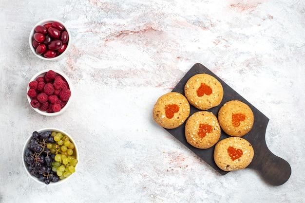 Vista dall'alto piccoli biscotti di zucchero deliziosi dolci per il tè con la frutta sulla superficie bianca torta biscotti zucchero torta dolce