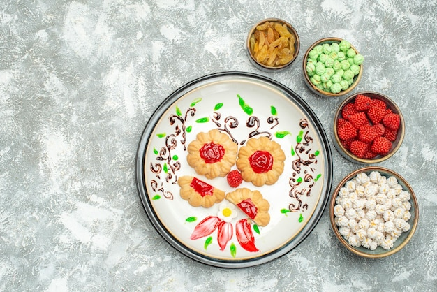 Top view of little sugar cookies with candies on white