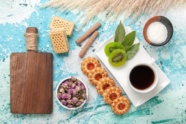 Вид сверху маленькое сахарное печенье с чашкой чая и вафлями на светло-голубом столе, выпечка бисквита, сладкий сахарный пирог, чай