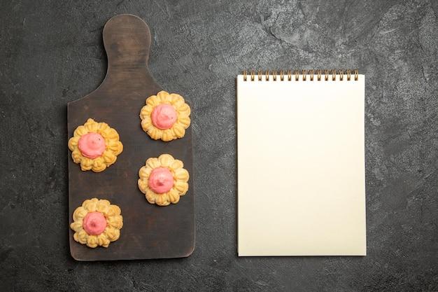 Vista dall'alto di piccoli biscotti di zucchero con crema di fragole sulla superficie grigia