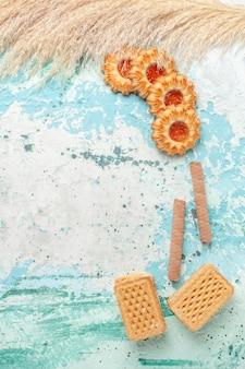 Vista dall'alto piccoli biscotti di zucchero con cialde sulla superficie blu