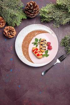 Vista dall'alto di piccoli biscotti dolci all'interno del piatto progettato su nero Foto Gratuite
