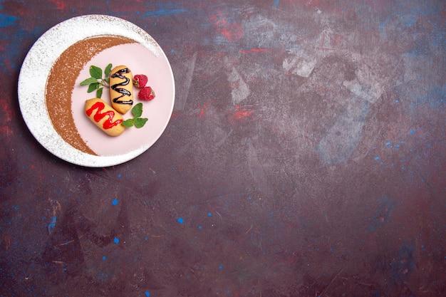Vista dall'alto di piccoli biscotti dolci all'interno del piatto progettato su nero