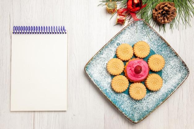 Vista dall'alto di piccoli biscotti dolci con torta di frutta all'interno del piatto sul tavolo bianco