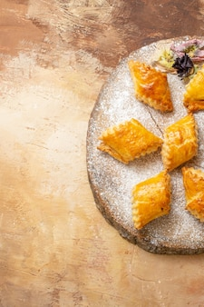 Top view of little sweet pastries for tea on light background