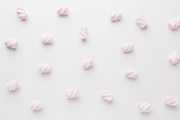 Вид сверху маленькие сладости на белом столе