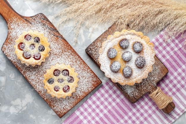 Vista dall'alto piccole gustose torte con frutta e zucchero a velo sulla scrivania bianca torta biscotto zucchero dolce