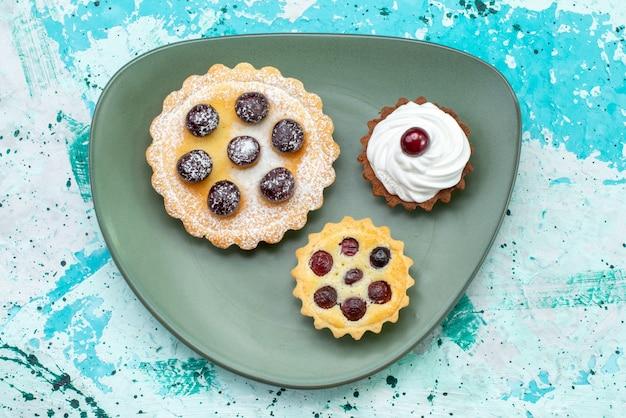 上面図青いテーブルケーキクリームフルーツスウィートティーのプレートの内側に砂糖粉フルーツクリームが入った小さなおいしいケーキ