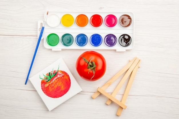 Vista dall'alto piccolo disegno di pomodoro con vernici colorate sul tavolo bianco