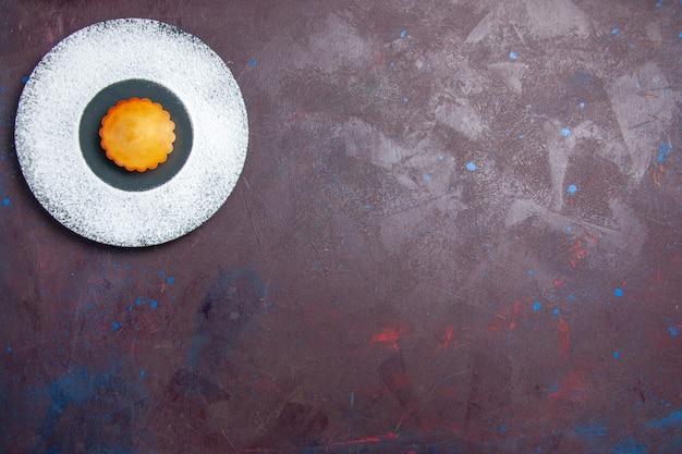 Vista dall'alto piccola torta squisita all'interno del piatto sulla superficie scura torta dolce biscotto biscotto tè torta