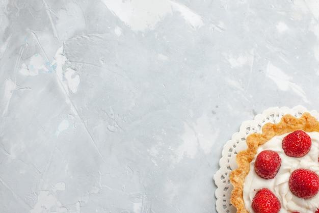 トップビューライトデスクケーキフルーツベリービスケットスイートクリームにクリームと新鮮な赤いイチゴと小さなおいしいケーキ