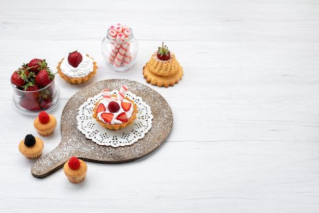 Вид сверху маленький вкусный торт со сливками и нарезанной клубникой пирожные на белом фоне торт ягодный сладкий выпечка с фруктами