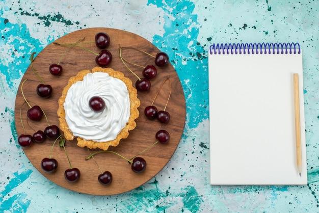 Vista dall'alto piccola torta squisita con crema e frutta sulla torta da tavolo blu-chiaro dolce crema infornare tè alla frutta