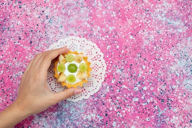 Vista dall'alto piccola torta gustosa con kiwi a fette di crema e banane sul biscotto dolce zucchero torta viola scrivania