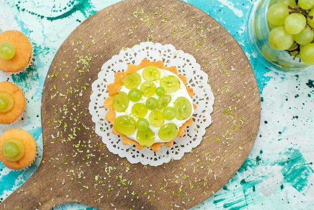 Vista dall'alto piccola torta gustosa con crema deliziosa e biscotti di uva fresca e affettata sulla foto dolce torta blu luce scrivania