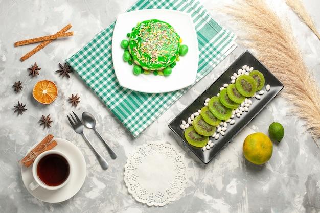 上面図白い表面にキウイとお茶を入れた小さなおいしいケーキシュガービスケットスウィートケーキベイククリームクッキー