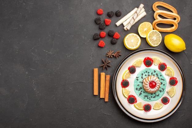 Vista dall'alto piccola torta squisita con fette di limone su sfondo scuro biscotto frutta torta dolce agli agrumi biscotto