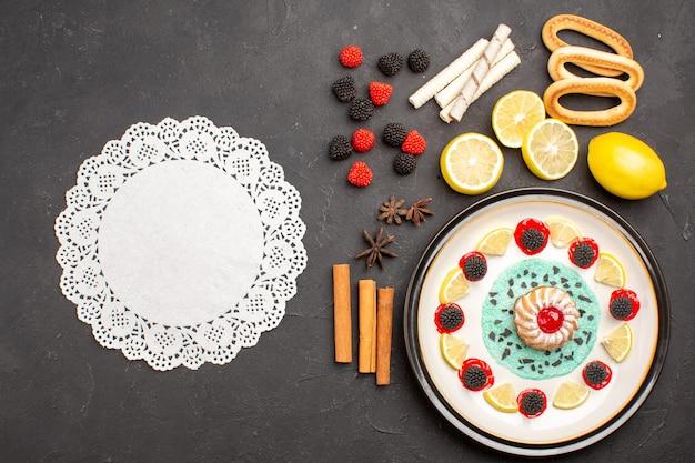 トップビュー暗い背景にレモンスライスと小さなおいしいケーキビスケットフルーツ柑橘系の甘いケーキクッキー