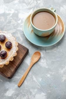 Vista dall'alto piccola torta gustosa con zucchero in polvere e ciliegie insieme a caffè al latte sulla scrivania leggera, torta di frutta, biscotto, dolce foto a colori