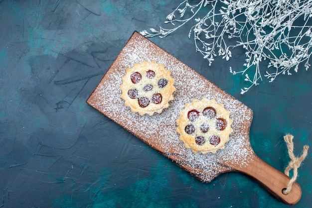 Top view little yummy cake with sugar powder and cherries on the dark-blue background fruit cake biscuit sweet photo color