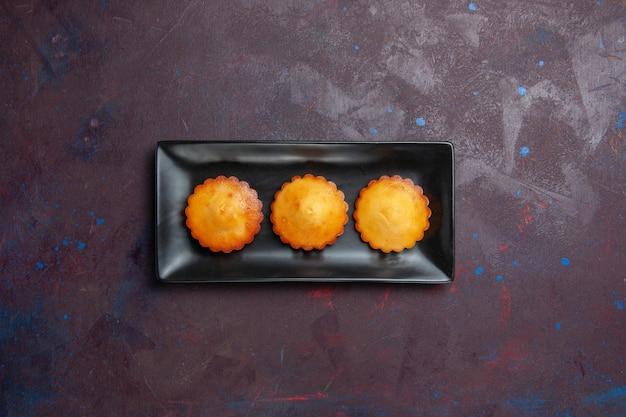 Vista dall'alto piccole deliziose torte all'interno di una tortiera nera su una superficie scura torta biscotto biscotto dolce zucchero tè