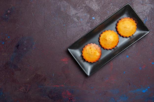 어두운 표면 파이 비스킷 케이크 달콤한 쿠키 차에 검은 케이크 팬 안에 작은 맛있는 케이크를 상위 뷰