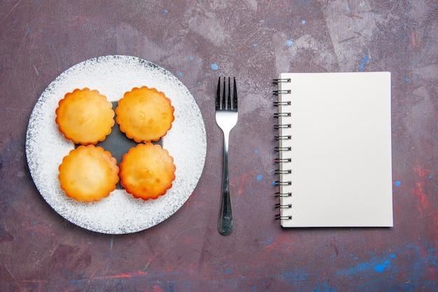 Vista dall'alto piccole deliziose torte all'interno del piatto sulla superficie scura torta di zucchero biscotto torta di biscotto dolce