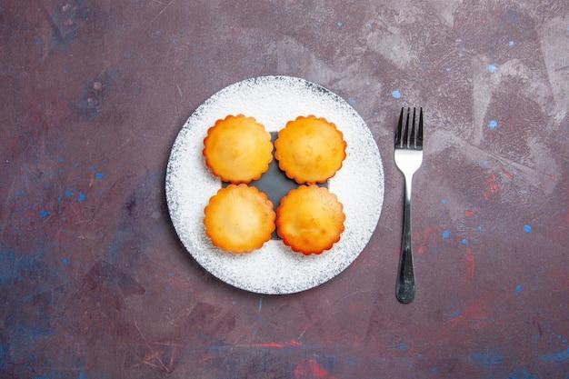 어두운 표면의 설탕 파이 비스킷 달콤한 쿠키 케이크에 있는 접시 안에 있는 작은 맛있는 케이크