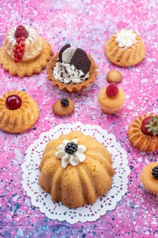 Vista dall'alto piccole torte gustose con crema insieme a diversi frutti di bosco sulla torta da tavolo luminosa e luminosa, biscotto, bacca dolce