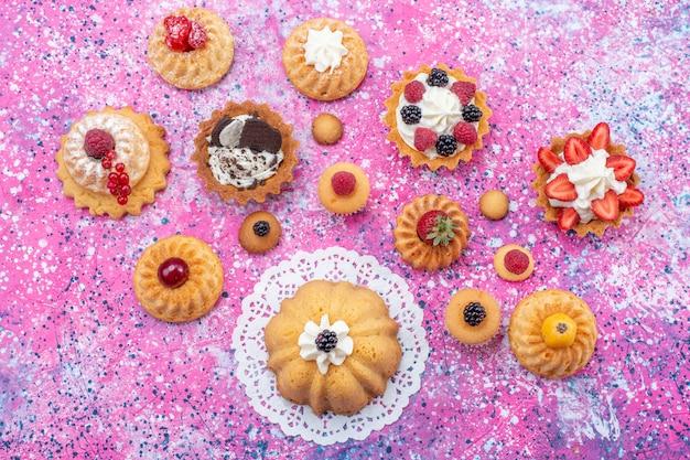 Vista dall'alto piccole deliziose torte con crema insieme a diversi frutti di bosco sul tavolo luminoso torta biscotto bacca dolce cuocere il tè