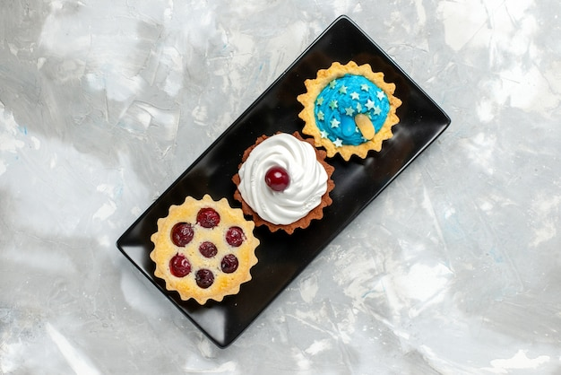Вид сверху маленькие вкусные пирожные со сливками и фруктами на ярком письменном торте со сладким кремом, выпечка фруктов