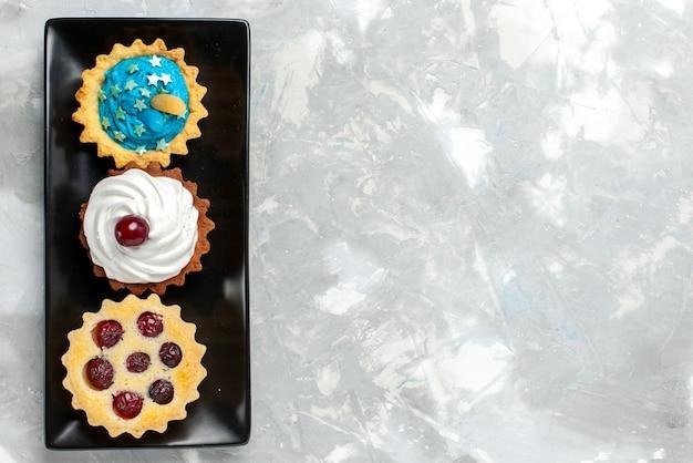 トップビュー明るい背景のケーキにクリームとフルーツの小さなおいしいケーキ甘いクリーム焼きフルーツティー