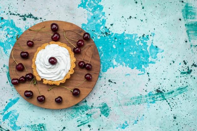 上面図水色の背景にクリームとフルーツの小さなおいしいケーキ甘いクリーム焼き茶