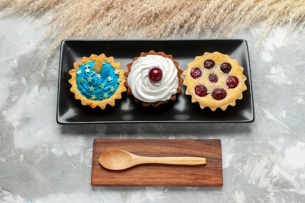 Вид сверху маленькие вкусные пирожные со сливками и фруктами на светлом столе, крем для торта, выпечка фруктовый чай