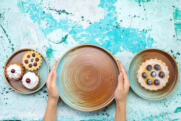 上面図水色の背景にクリームとフルーツの小さなおいしいケーキ甘いクリーム焼きフルーツ