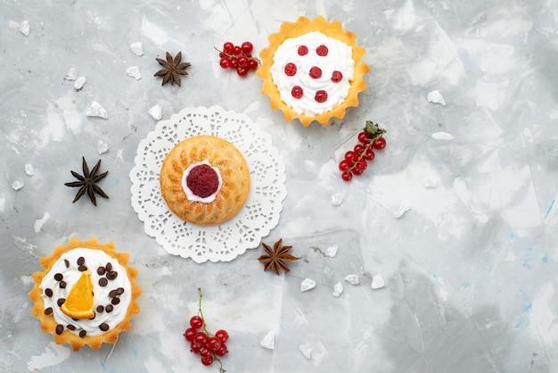 Вид сверху маленькие вкусные пирожные со сливками и красными фруктами на сером письменном столе сладкий бисквитный сахарный крем