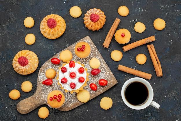 暗い机の上にクリームシナモンコーヒーと新鮮なフルーツと小さなおいしいケーキのトップビュー甘いビスケットケーキデザートフルーツベリー