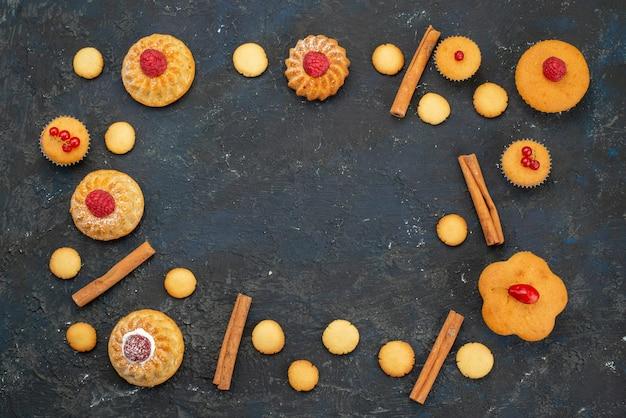 暗い机の上のクリームクッキーシナモンと上面の小さなおいしいケーキ甘いビスケットケーキデザートフルーツベリー