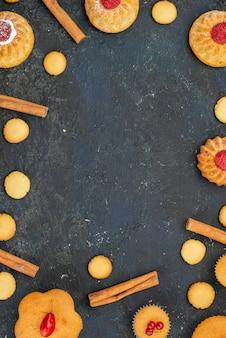 上から見る暗い机の上にクリームクッキーシナモンと少しおいしいケーキ甘いビスケットケーキデザートフルーツ