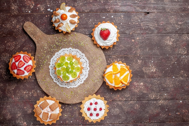 Top view little yummy cakes with cream and different sliced fruits on the wooden brown background fruit cake biscuit sweet bake photo