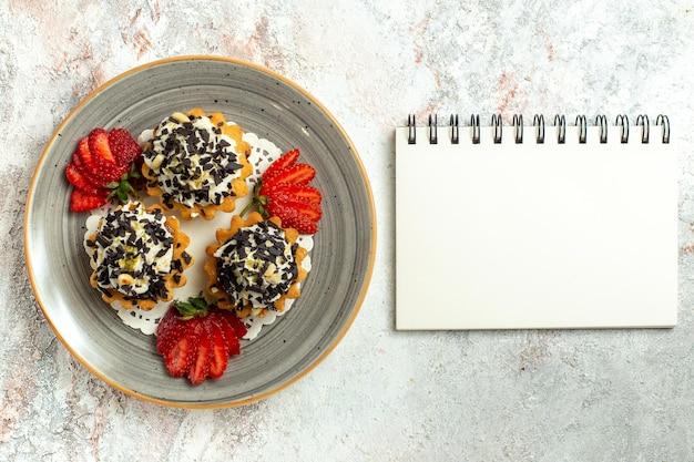 Vista dall'alto piccole deliziose torte con crema e fragole su superficie bianca festa di compleanno torta biscotto dolce