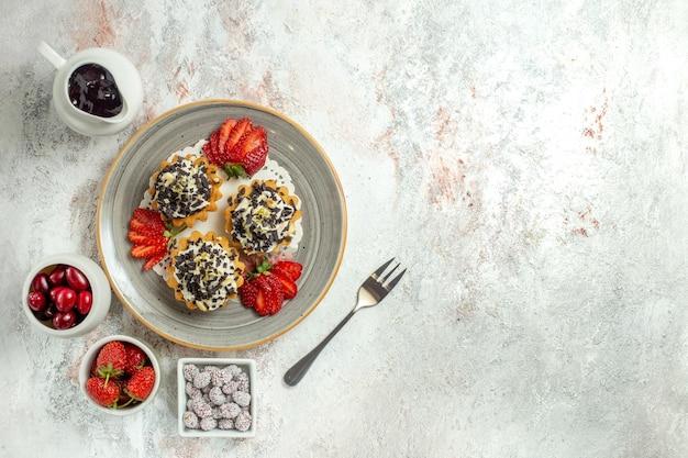 Vista dall'alto piccole deliziose torte con crema e fragole sulla superficie bianca festa di compleanno torta di biscotti dolci