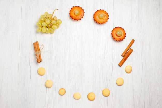 Вид сверху маленькие вкусные пирожные с виноградом и печеньем на белом столе, фруктовый торт, бисквит, сладкий десертный чай