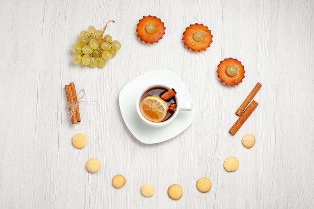 Вид сверху маленькие вкусные пирожные с виноградом, чашка чая и печенье на белом столе, фруктовый торт, бисквит, сладкий десертный чай