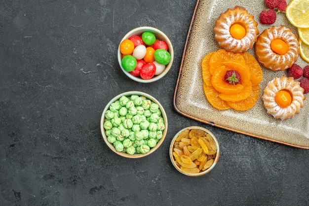 Top view of little yummy cakes with lemon slices tangerines and candies on dark