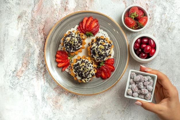 Vista dall'alto piccole deliziose torte con fragole e caramelle su superficie bianca festa di compleanno torta di biscotti dolci