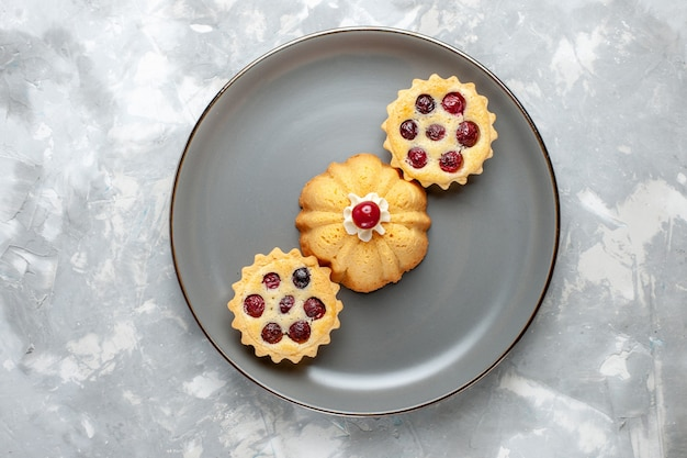 Вид сверху маленькие вкусные пирожные с сахарной пудрой и вишней на светлом столе фруктовый торт бисквитный сладкого цвета
